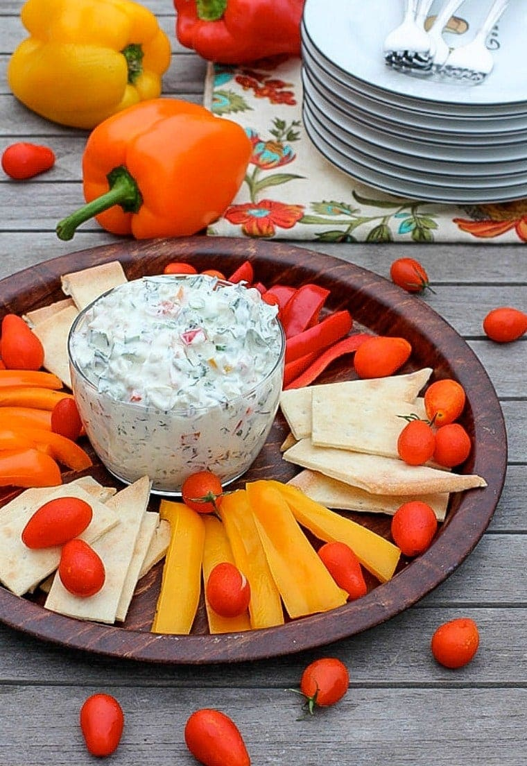 veggie dip with greek yogurt + bell peppers and pita brea on a platter