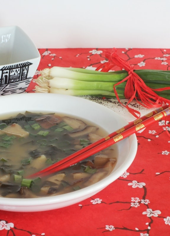 sea vegetables soup in a white dish with red chopsticks