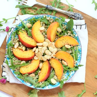 Arugula Salad with Peaches and almonds on a blue and white plate
