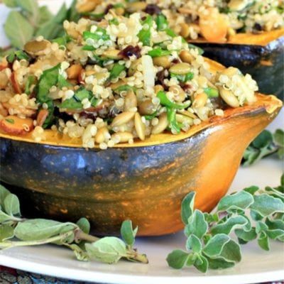 vegetarian stuffed acorn squash with fresh oregano on a white platter