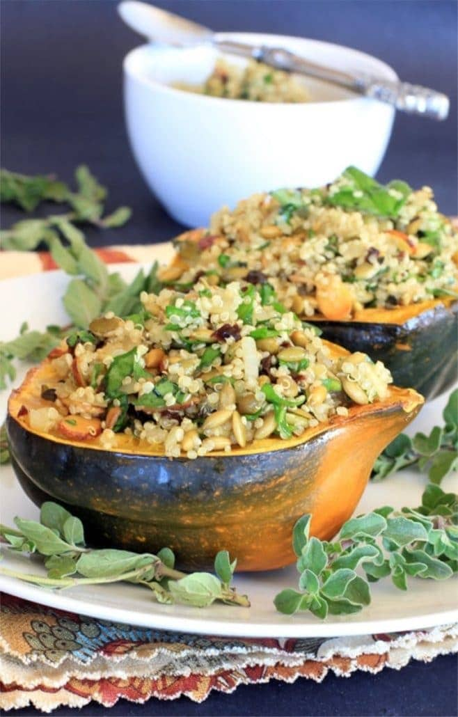 vegetarian stuffed acorn squash with quinoa pilaf on a white platter