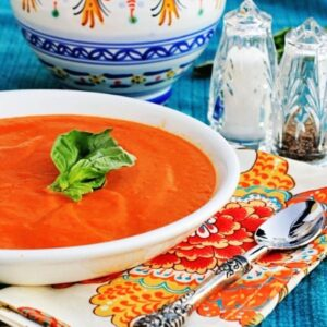Cream of tomato soup in a white bowl with a colorful napkin in the background.