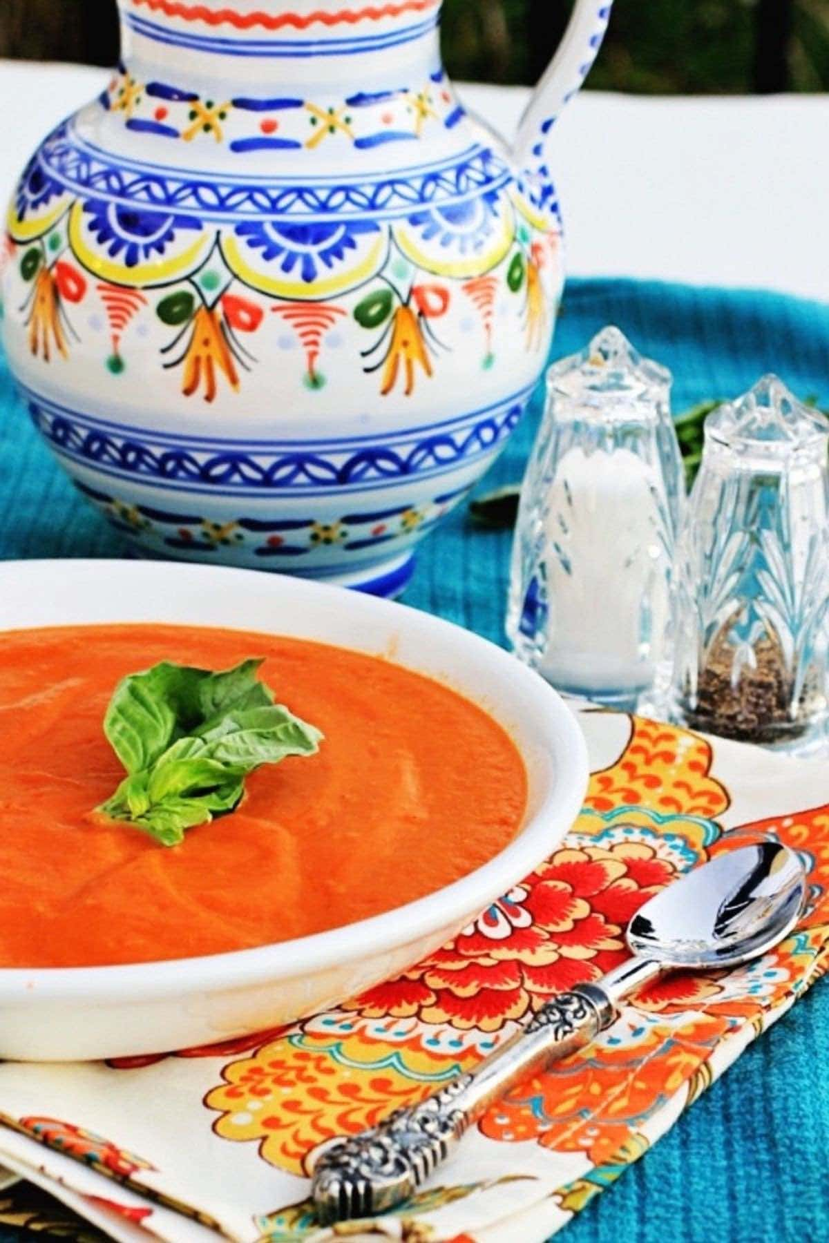 Healthy Cream of Tomato Soup ina white bowl with fresh basil on top.