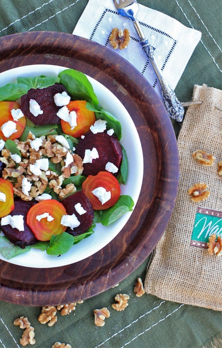 Roasted beet salad with goat cheese, walnuts, and greens in a white bowl on a wood tray