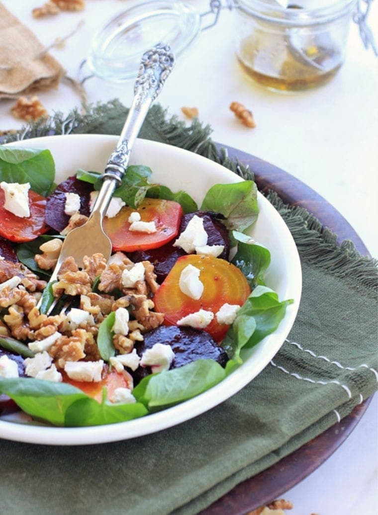 beet salad with greens, walnuts, and goat cheese in a white bowl with a fork.