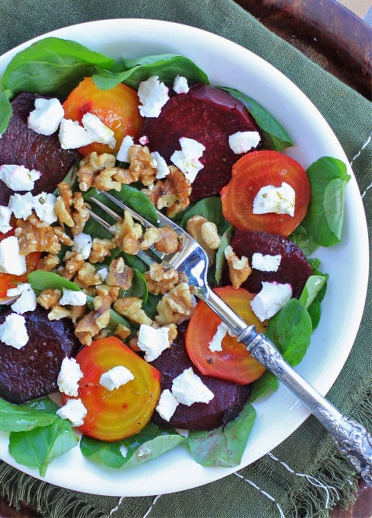 Roasted Beet Salad with Goat Cheese, walnuts, and greens in a white bowl.