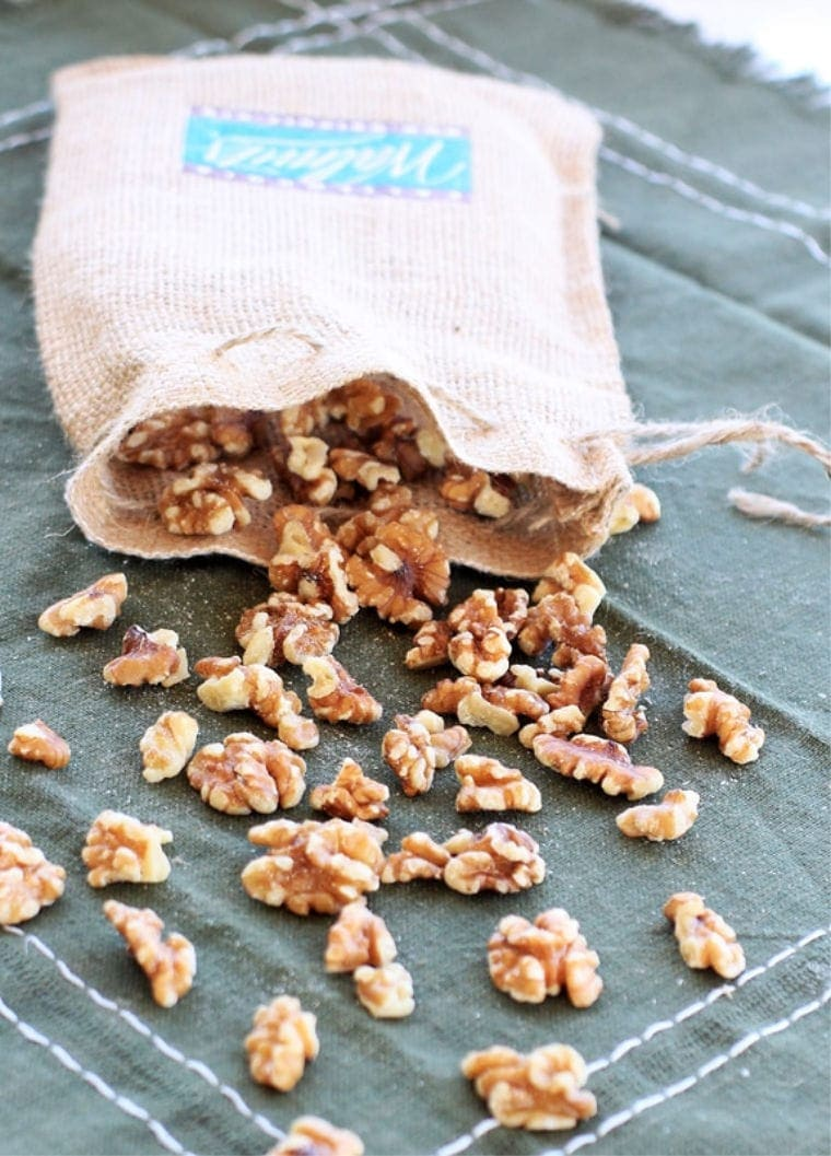 walnuts falling out of a burlap bag on a green napkin