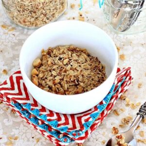 Low FODMAP granola in a white bowl on a red and white chevron striped napkin.