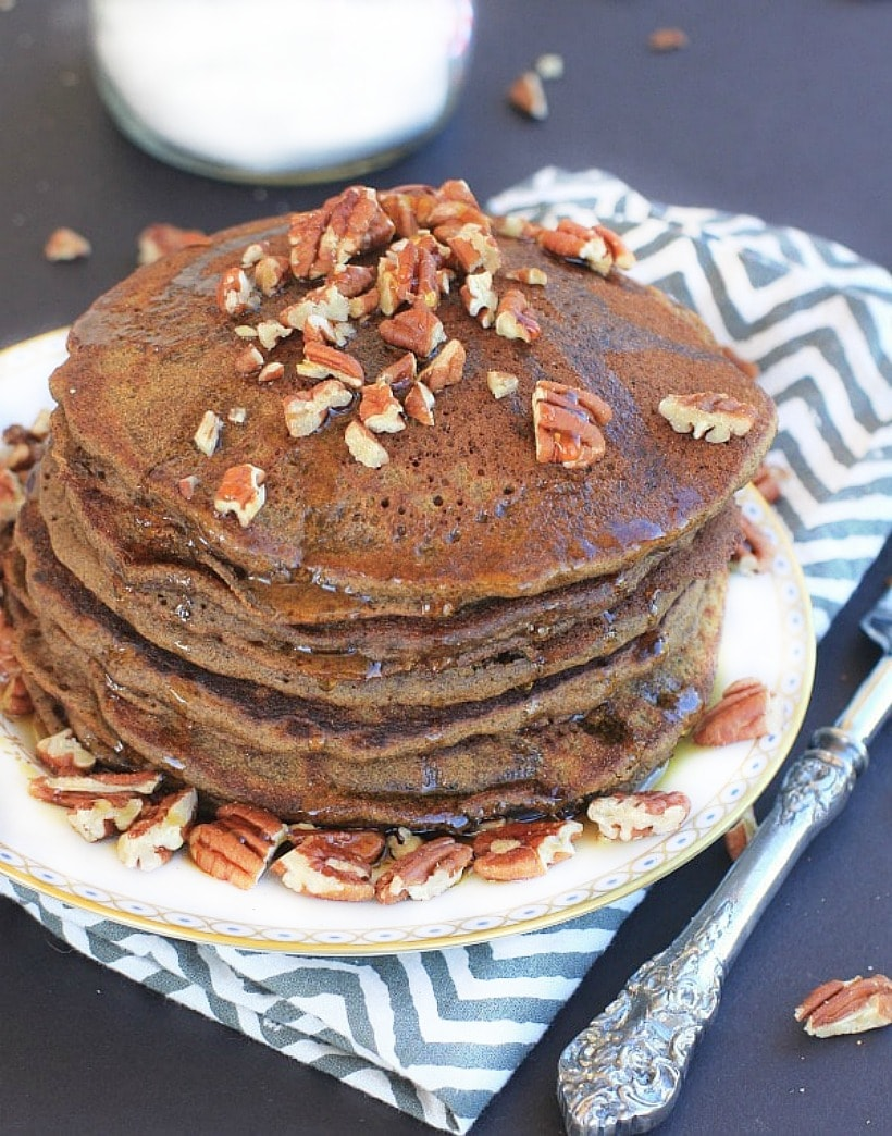 Gluten Free Gingerbread Pancakes on a plate topped with pecans and maple syrup.