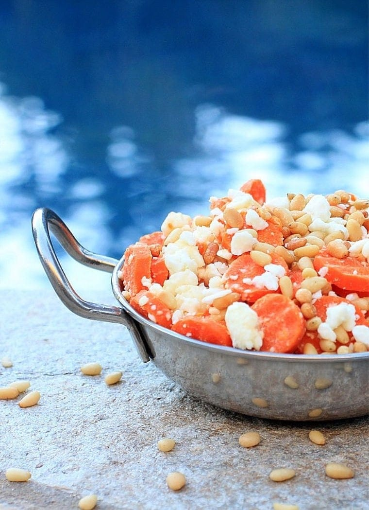 Steamed carrots with feta and pine nuts in a serving dish.