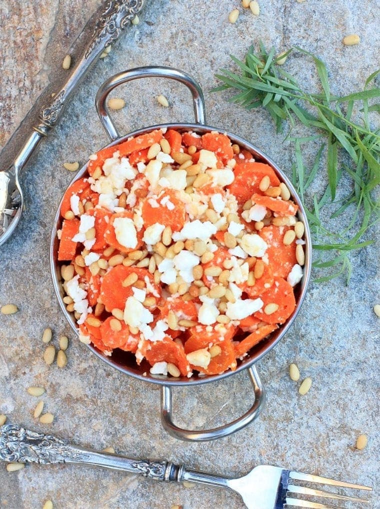 Steamed Carrots with feta and pine nuts in a serving bowl.