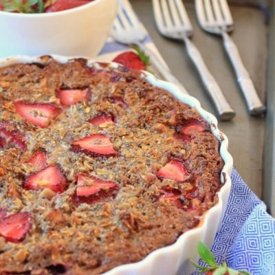 Baked oatmeal Chia pie in a white tart pan with strawberries on top.