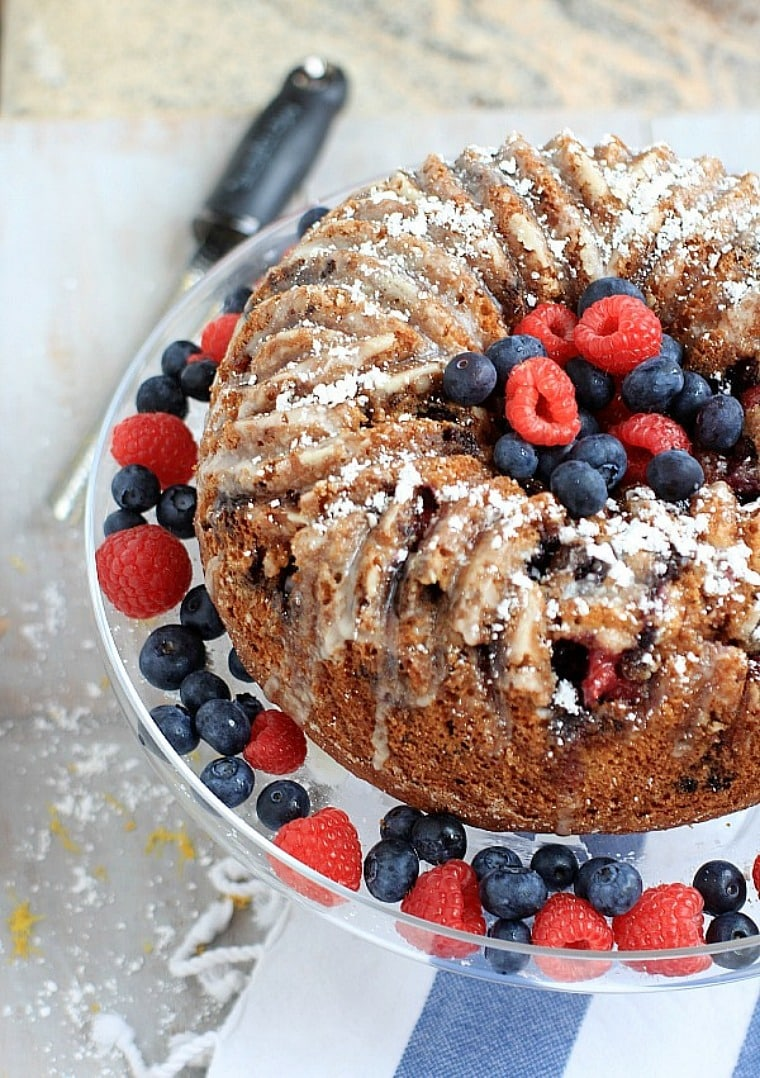 lemon bundt cake on a glass cake stand with blueberries and raspberries