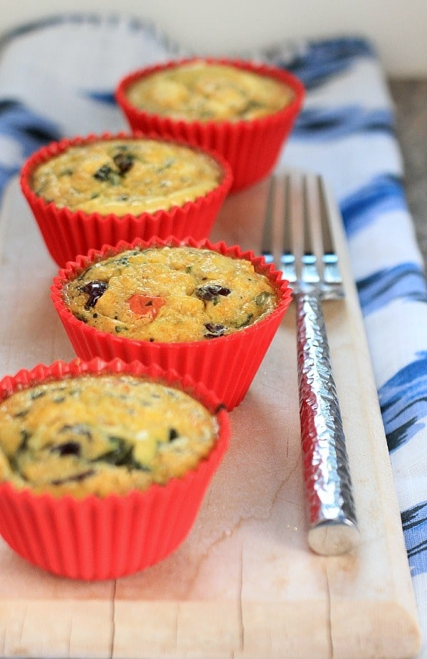 Low Carb Egg Muffins - 4 of them on a wooden tray with a fork and blue napkin.