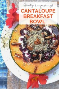 Cantaloupe breakfast bowl in a white bowl with cottage cheese, berries, hemp seeds, and pecans