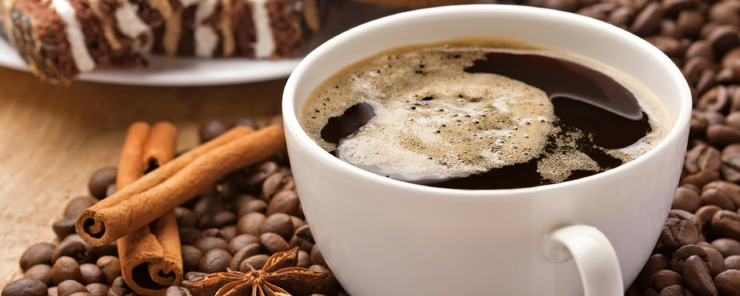 Coffee cup, cinnamon, anise on coffee beans, sweets on the background