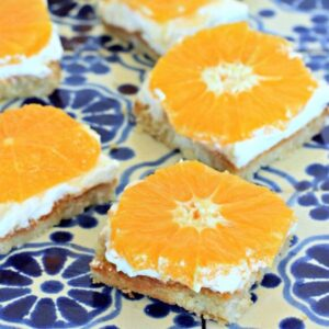 orange honey cheesecake bars on a blue and white tiled tray.