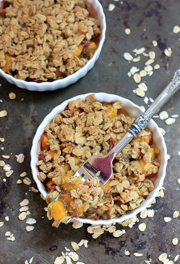 gluten free peach crisp in white ramekins with fork