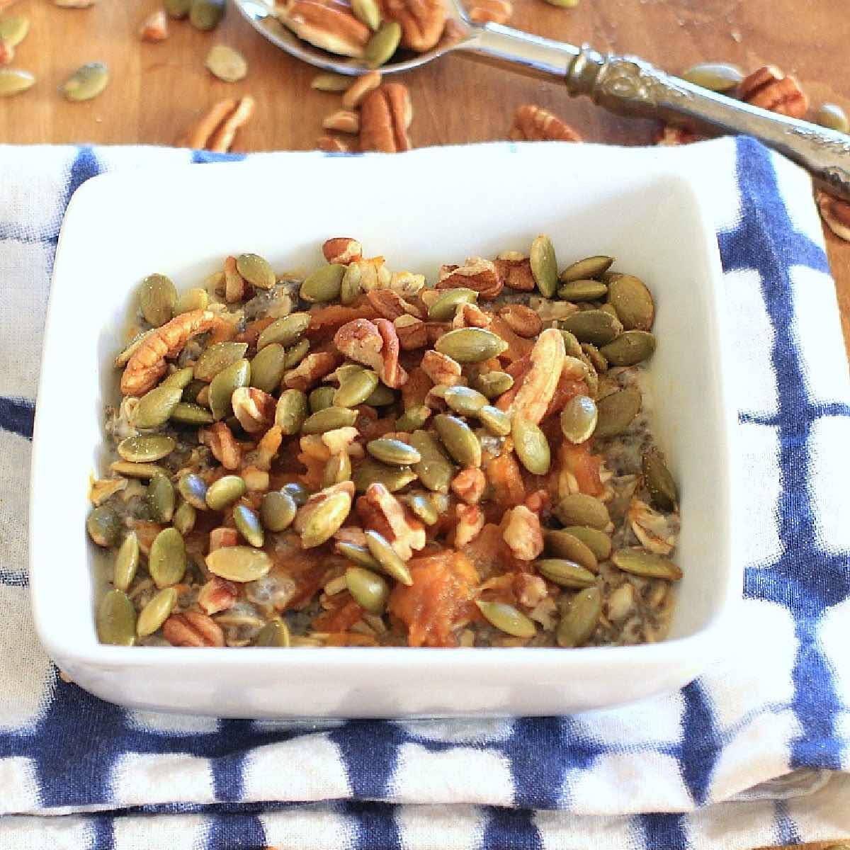 Oatmeal in a white bowl topped with pumpkin seeds and pecans.