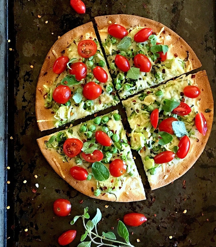 This Brussels Sprouts, Green Pea, and Cherry Tomato Pizza will quickly become you're new favorite! Topped with Parmesan cheese and fresh oregano, it's absolutely delicious! | Gluten Free Brussels Sprouts recipes @thespicyrd