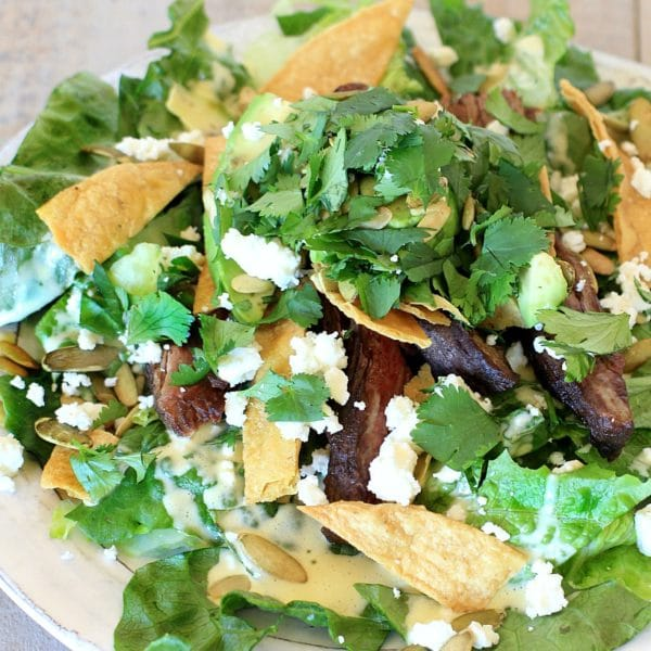 This healthy taco salad with easy homemade Caesar salad dressing, creamy avocado, crunchy pumpkin seeds, and {optional} pan seared flank steak is a delicious new twist for #TacoTuesday !