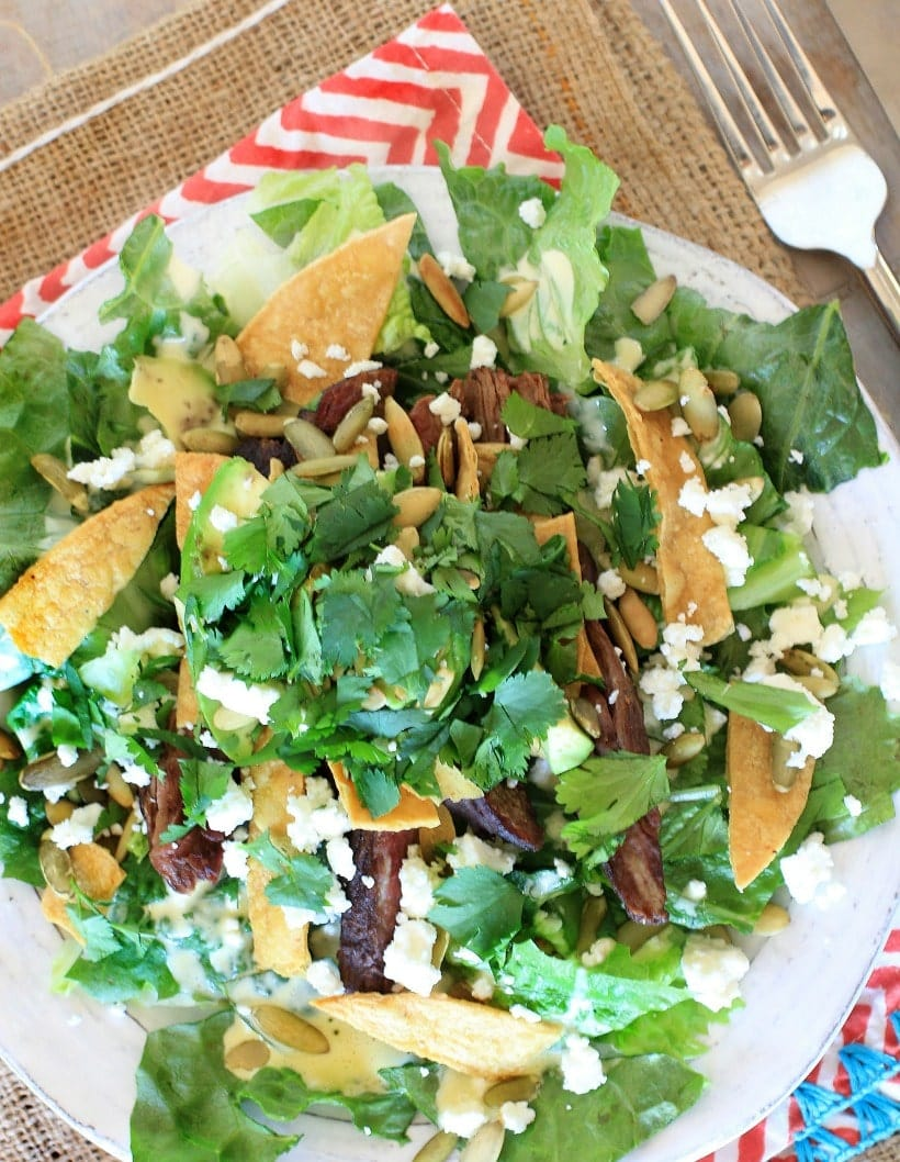 his healthy taco salad with easy homemade Caesar salad dressing, creamy avocado, crunchy pumpkin seeds, and {optional} pan seared flank steak is a delicious new twist for #TacoTuesday !