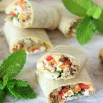 This Sabra Hummus Veggie Wrap is powered with plant based protein + peppers, roasted eggplant, fresh mint, & feta cheese~perfect for a healthy, yet filling lunch, snack, or appetizer! Get the gluten-free recipe at EA Stewart, The Spicy RD #sponsored