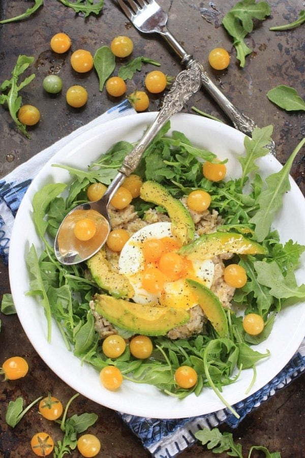 This Sunshine Savory Oatmeal w/ Egg, Arugula, Tomatoes, and Avocado, is the ultimate healthy comfort food for breakfast, or any meal of the day! Get the gluten free and vegetarian recipe at EA Stewart, The Spicy RD @thespicyrd