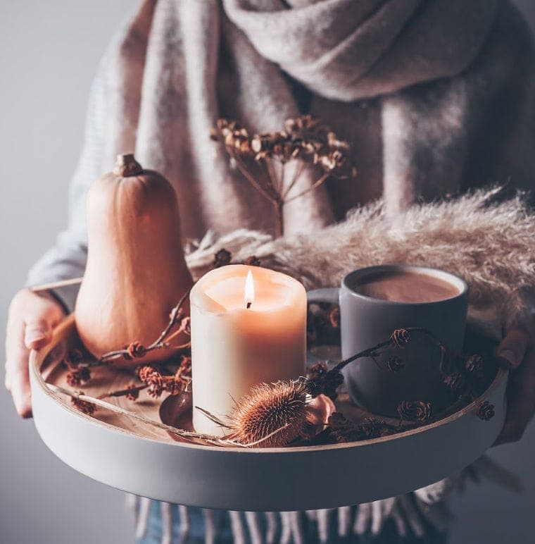 Candles and hot chocolate on a serving tray.