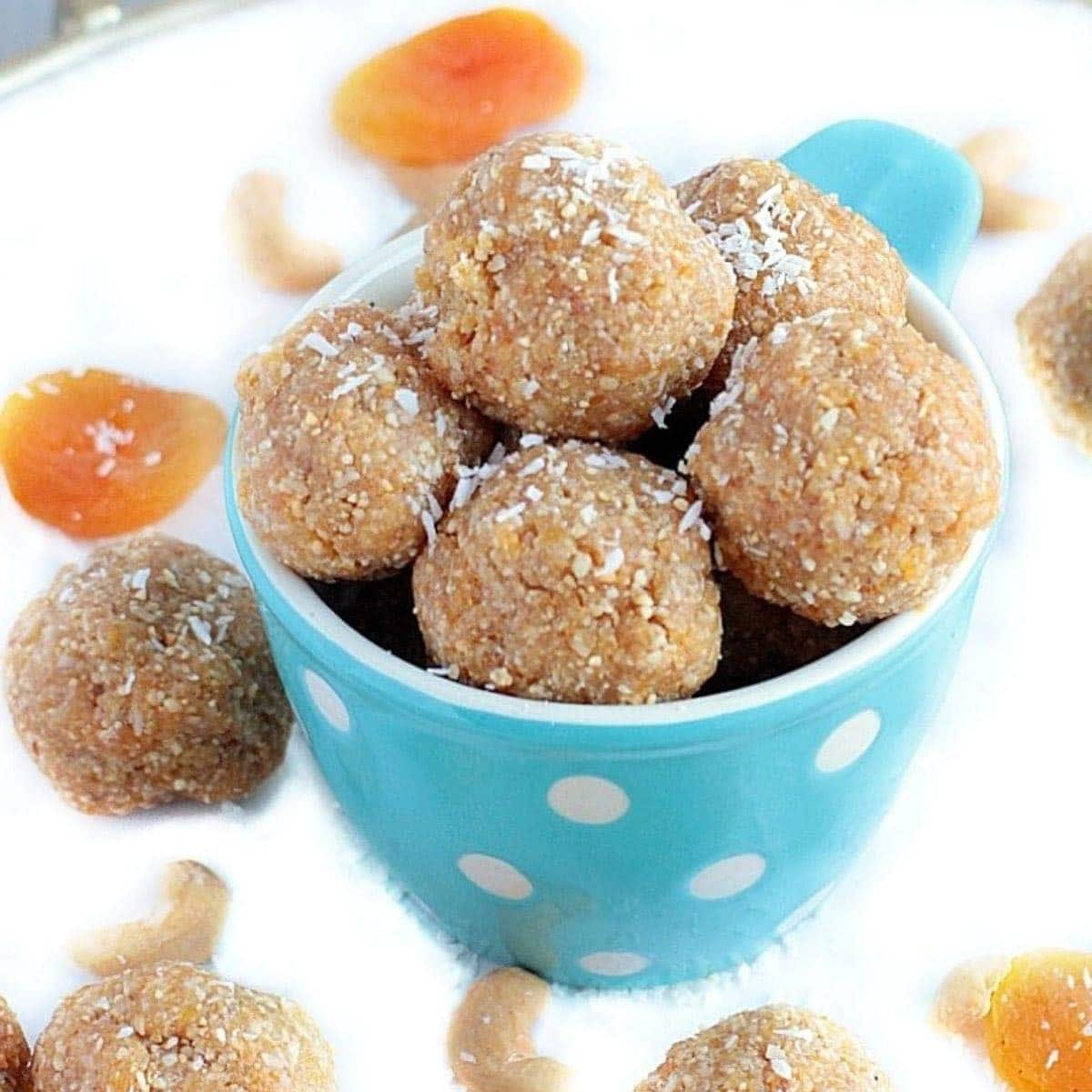Blue bowl with polkadots filled with apricot energy bites.