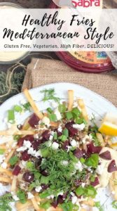 flat lay photo of french fries on a white plate topped with beets, hummus sauce, dill, green onions, and feta
