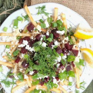 healthy loaded fries on a white plate topped with beets, feta cheese, and fresh dill
