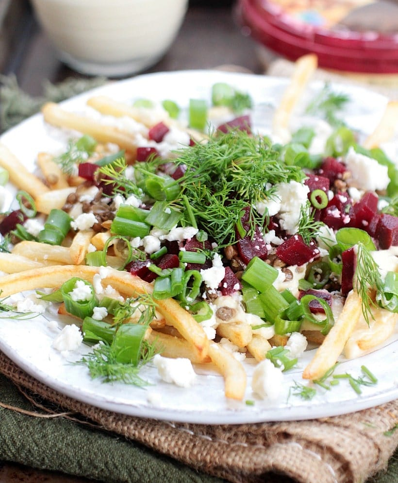 healthy fries on a plate with beets, feta cheese, green onions, dill, and hummus sauce.