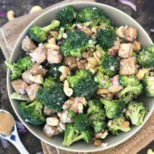 Healthy Broccoli Salad with Cashew Nuts in a green bowl.