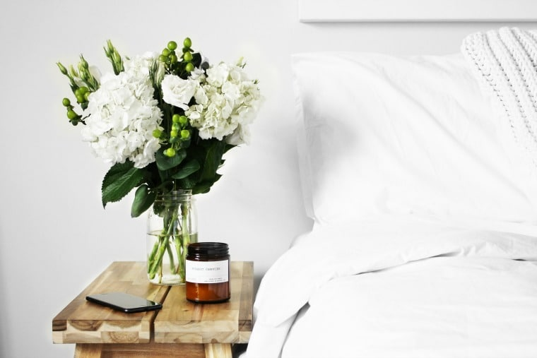Natural sleep tips ~ Bed with white sheets, wood side table, flowers, and candle