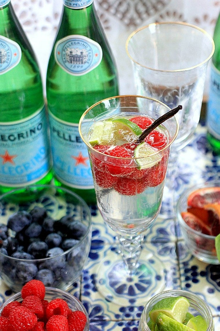 sparkling water in a glass with raspberries and lime