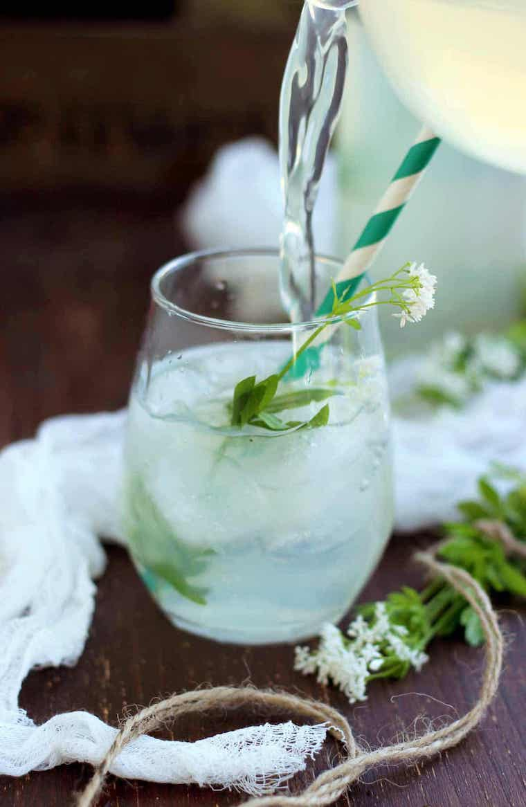 pretty sweet woodfuff lemonade being poured in a glass with wild flowers and a straw