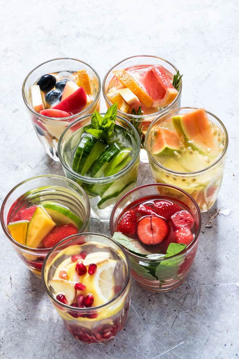 7 glasses with water, fruits, and herbs