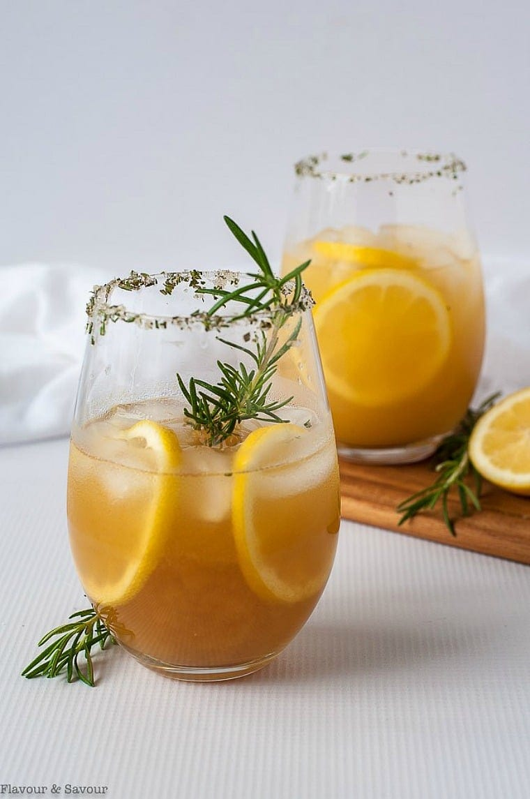 healthy mocktail recipes - pineapple ginger kombucha mocktail with rosemary in 2 glasses