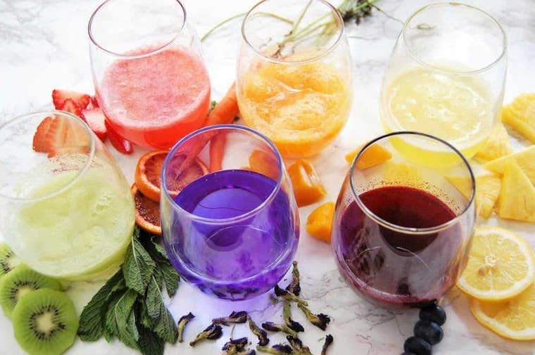 7 glasses with colorful fruit juices