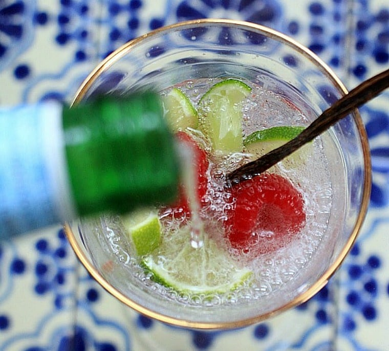 sparkling water being poured into a glass with lime and raspberries