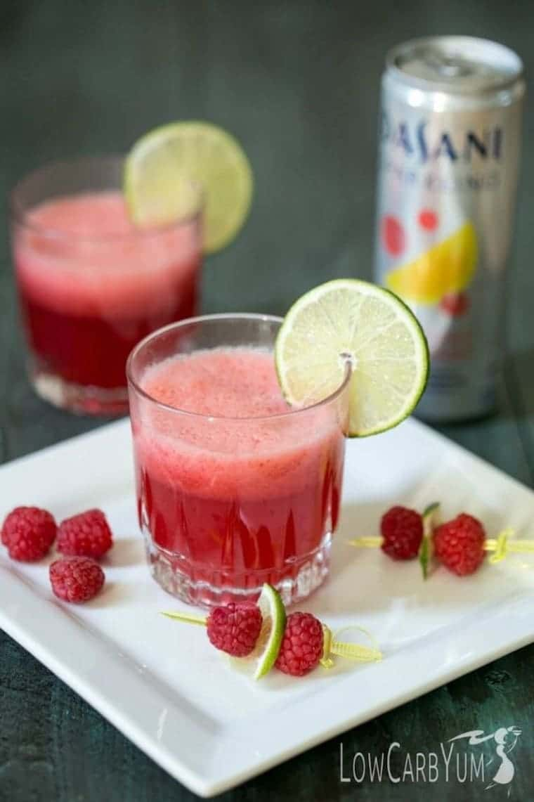 2 glasses of sparkling raspberry limeade with fresh raspberries and lime slices