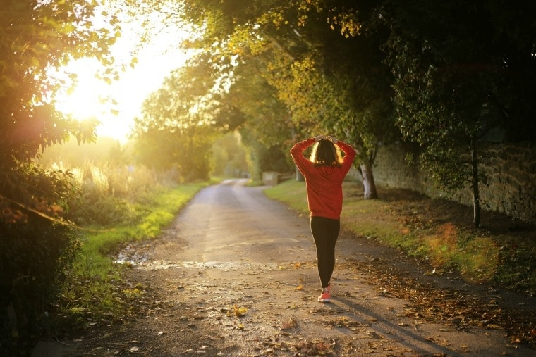 how to boost your metabolism photo of a woman walking outside on dirt path with trees
