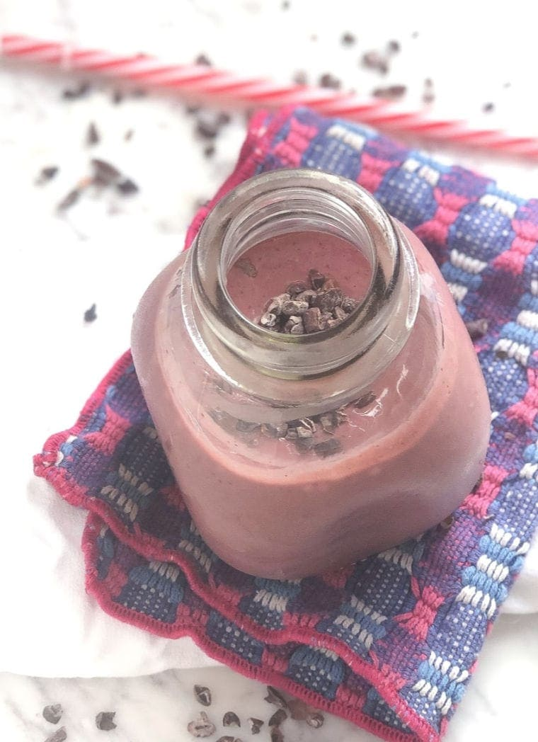 Chocolate Cheesecake Cherry Smoothie in a glass jar with cacao nibs and a straw in the background.