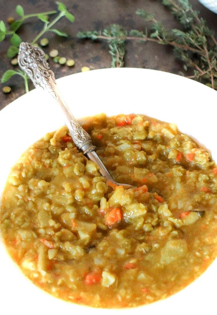 Vegan Split Pea Soup in a white bowl with fresh herbs