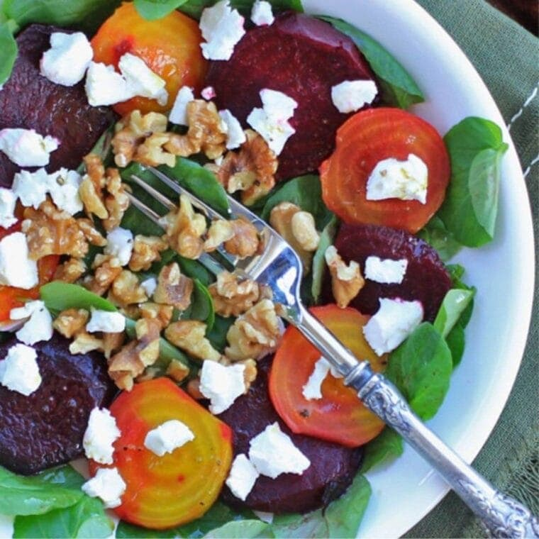 white bowl with toasted beet salad topped with walnuts and greens.