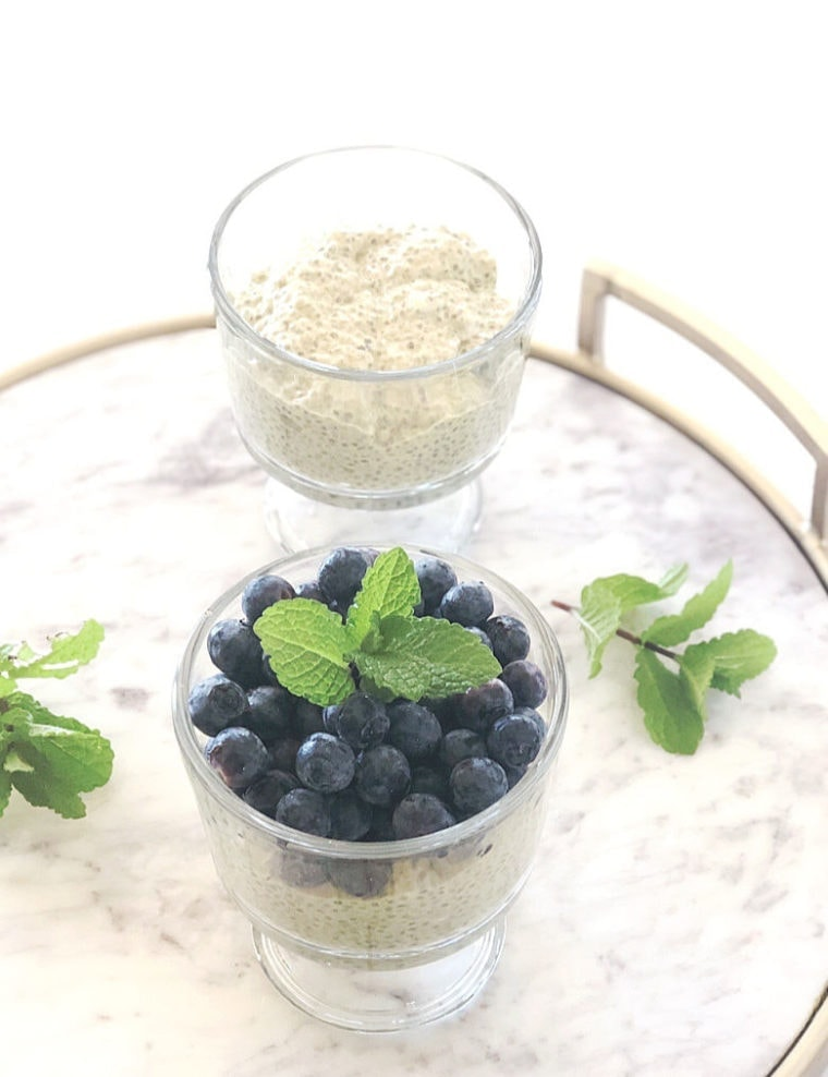 Coconut Chia Pudding with blueberries and mint on marble tray.