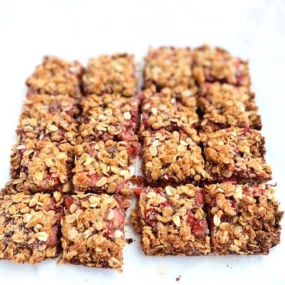 Strawberry Oatmeal Bars cut into squares on white parchment paper