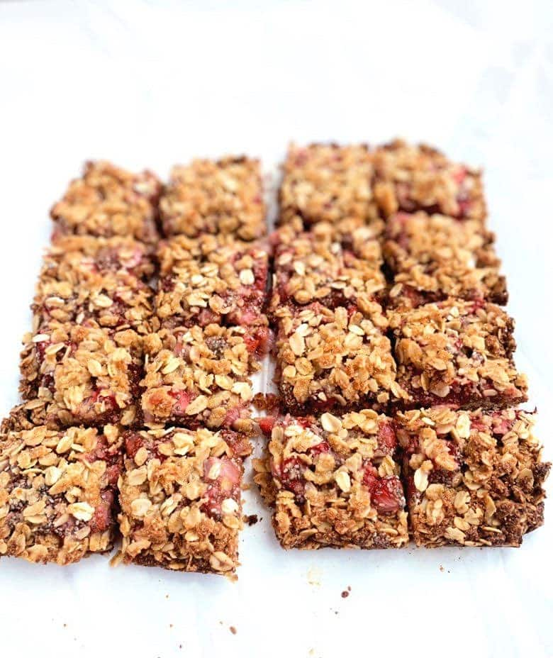Strawberry oatmeal bars cut into slices on white parchment paper.
