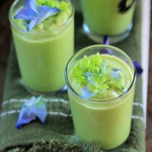 cucumber avocado soup in shot glasses with purple flowers on top.
